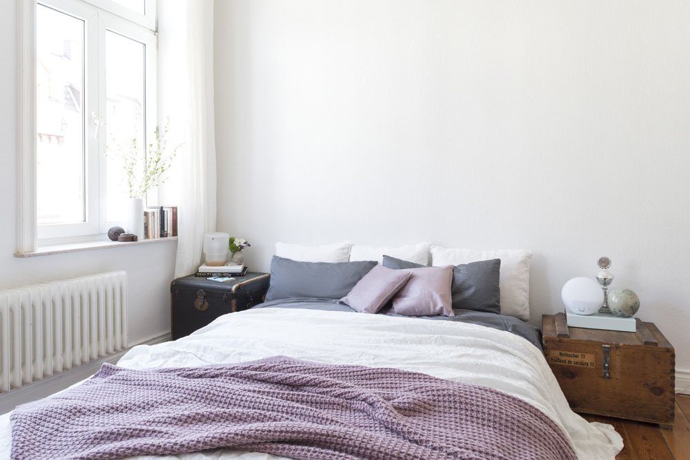 Johanna mixt gerne unterschiedliche Stoffe – der Material- und Farbmix auf dem Bett ist ihr perfekt gelungen: In ihrem Bett kombiniert sie weiße Leinenbettwäsche mit grauer Satinbettwäsche, fliederfarbenen Kissen mit Muster und Samtrückseite und einem Strickplaid mit Alpaka-Anteil – alles außer weißer Bettwäsche von JOOP! Living.